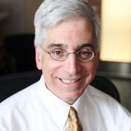 Caucasian male doctor, short white hair, hospital room in the background.  Shown from shoulders up, smiling showing teeth.  Long face, clean shaven.  White shirt and gold toned tie.  Wearing oval shaped glasses.
