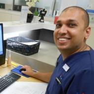 Male clinical nurse sitting at his desk in front of his computer monitor.  Dark complexion, receding hairline, closely shaven head, wearing dark blue scrubs and watch on left wrist.  Shown from waist up in picture.  Smiling towards the camera at an angle from the right side of the photo.