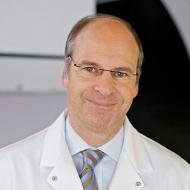 Caucasian doctor standing in front of a window, shot from shoulders up.  Receding hairline with light colored, short hair.  Smiling, lips closed. Long face, wearing glasses.  Wearing light blue shirt, tie, and lab coat over it.