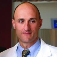 Caucasian doctor facing camera, headshot from shoulders up.  Office in the background. Wearing light blue shirt with tie, and lab coat on top.  Receding hairline, very short dark hair. Sharp features, serious, no smile.